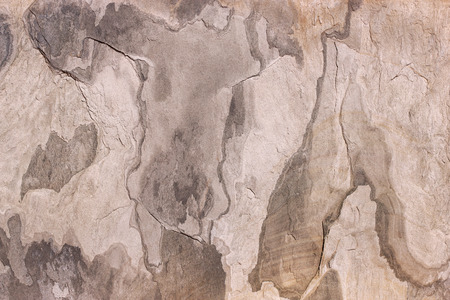 Abstract pattern of a stone plate in beige, gray and brown. The slab is part of a wall covering in La Gomera, Spain.