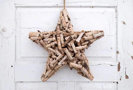 close p: A handcrafted star made of natural, short cut branches hangs on an old, white-painted door. The color is dirty, cracked and peeled off Partially already.