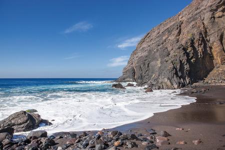 Lonely beach with black sand and impressive rock backdrop at the Playa del Trigo near Alojera in the west of La Gomera, Canary Iceland, Spain. Banco de Imagens