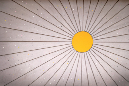 vignetting: Sun-shaped, bright, slightly dirty wooden wall with small light colored points and vignetting