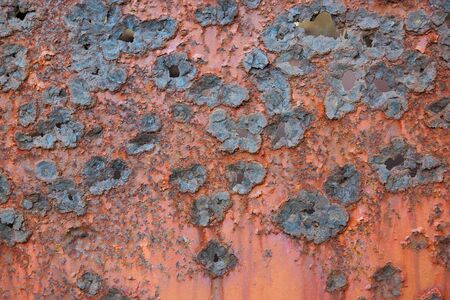 holey: Detail shot of a rough, blue, flower-shaped and Partially holey texture on a orange, rusty metal plate