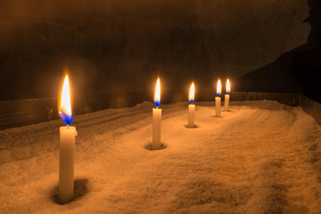 votive: Five lighted, small, white votive candles on a sand-filled metal table in a dark room
