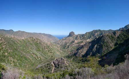 cano: The elongated valley of Vallehermoso, La Gomera, Canary Islands, Spain, northbound. In the middle the distinctive rock summit Roque El Cano.