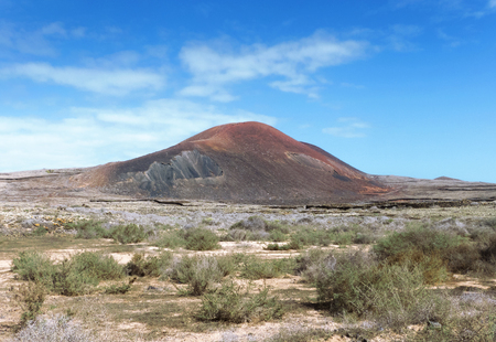 hondo: The red-colored Montana Colorada in the north of Corralejo in Fuerteventura, Canary Islands, Spain. Around this mountain and the volcano behind Calderon Hondo goes the famous volcanic path of Corralejo.