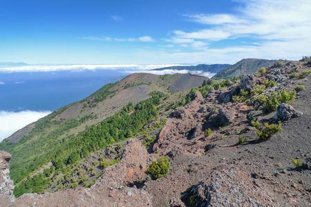Uitzicht over het westen van El Hierro: aan de rechterkant de vlakke Malpaso met mast, achter de rotswand van de El Golfo-vallei. Op de achtergrond links La Palma, Tenerife rechts.