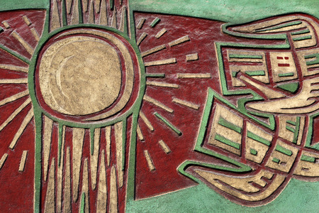 close p: Architectural detail on a facade: old artistic sun relief in red, green and beige Stock Photo