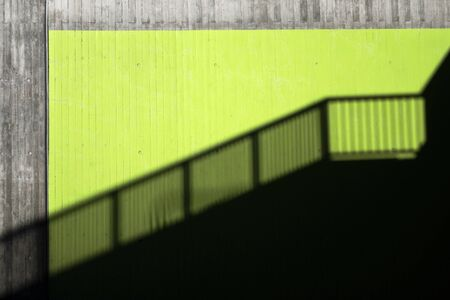 exposed concrete: Shadow of a banister on a green wall of exposed concrete in a city