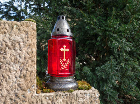 honeycombed: A red grave lantern with golden cross stands on a stone in front of a conifer