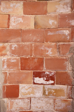 close p: Detail shot of a semicircular, smudged, Roughly carved wall of reddish bricks
