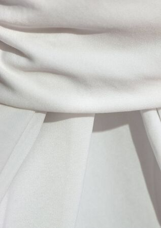draped cloth: Detail of a draped, elaborate pleated white table cloth of a slightly textured cloth