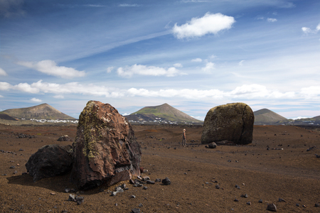 hugh: Hugh volcanic bombs in the volcanic landscape of Lanzarote, Canary Islands, Spain. A hiker with a body height of 5\\\\\\\8 stands beside and looks fascinated.