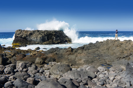 natural force: A man stands on a rocky coast and photographed the high splashing breakers on a big rock - taken on the northwest coast of Lanzarote, Canary Islands, Spain.