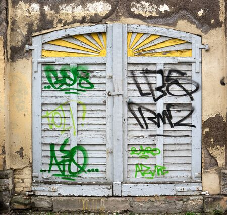 daubed: A closed, old, gray, wooden window shutter in a dilapidated facade was smeared with green and black graphic characters.