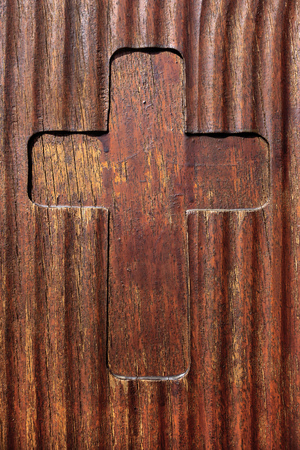 sacral symbol: Cross that was milled in a slightly corrugated and with brown color varnished wooden board.