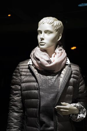 anorak: Upper body of a female mannequin with a gray quilted anorak and a round the neck wounded scarf in front of a dark background Stock Photo