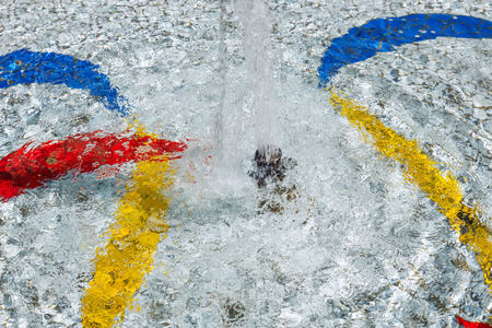 fluent: Detail of a small fountain with a spout and a colorful pattern of yellow, blue and red curves at the bottom of the white water basin