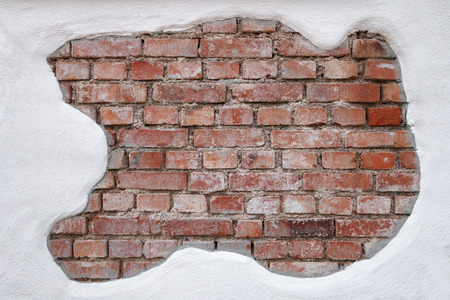 partially: Old, strongly dirty, red brick wall, that was partially covered with white plaster, taken in close-up.