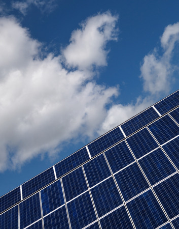 slant: Blue solar cells in slant perspective against blue and white sky