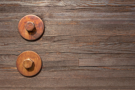 mounted: Two big brown hexagon bolts with integrated washer are mounted one above the other on a slightly weathered wooden wall