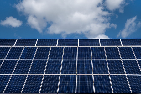 solarcell: Blue solar cells with white border against blue and white sky. Allover mounted on a rearwardly inclined roof area. Stock Photo