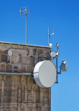 mounted: Several modern antennas are mounted on the upper corner of an old industrial building taken with a cloudless blue sky.