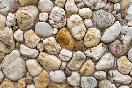 pebblestone: Detail shot of a natural stone wall of bright gray beige and light brown rounded pebble stones