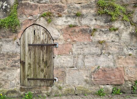 mountings: Small round weathered wooden door with iron mountings in an old masonry Which is Partially overgrown with plants.