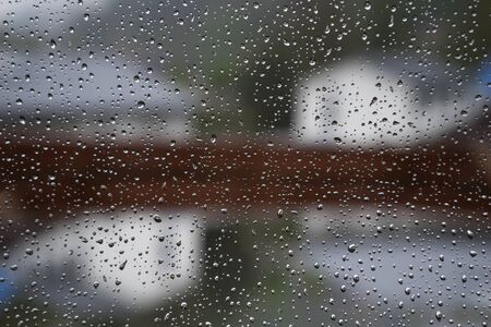 tristesse: Raindrops on a window pane in Which the rainy outdoor area is reflecting. In the background the blurred contours of the houses of a settlement.