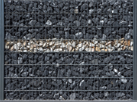 gabion: Gabion filled with dark anthracite stones and a bright horizontal stripe of beige stones
