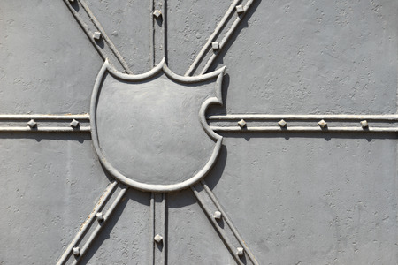 struts: Empty blazon on a gray painted rough metal door with decorative struts. Partially with light rust. Stock Photo