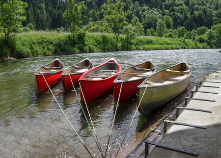 Five Tied empty canoes lie in a row next to eachother in a river on a fortified landing stage on the shore. Stock Photo