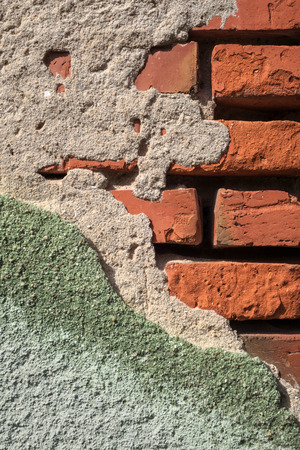 Crumbled green gray plaster on a red brick wall