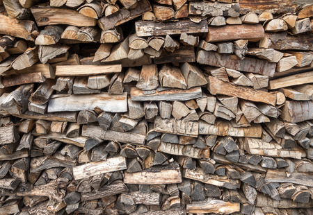 varying: Stacked, short, brown and gray firewood with varying stacking patterns