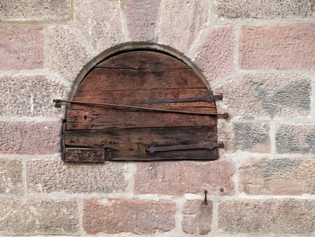 mountings: Round small wooden door in an old masonry Stock Photo