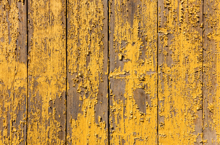 spall: Yellow paint is peeling from a board wall