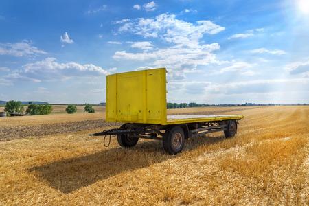 stubble field: Yellow trailer in a stubble field
