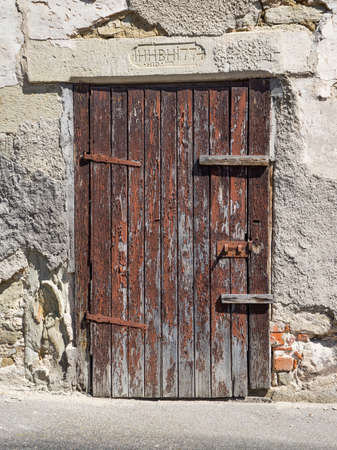 spall: Old, heavily weathered, brown wooden door