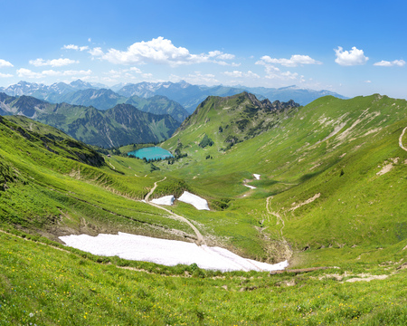 allgau: Last snow remains in the summer Allgau Alps with lake Seealpsee Stock Photo