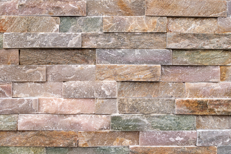 facing a wall: Stone wall of pastel-colored facing stones