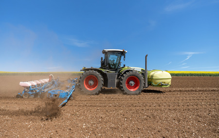 sowing: Tractor with sowing machine Stock Photo