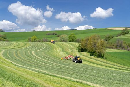 fodder: Two tractors at the harvest of green fodder