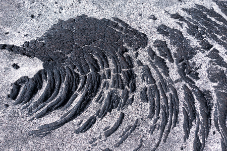 Detail of black, solidified pahoehoe lava with sand