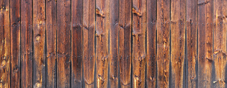 Panorama of a dark brown wooden wall with two rows of of nails