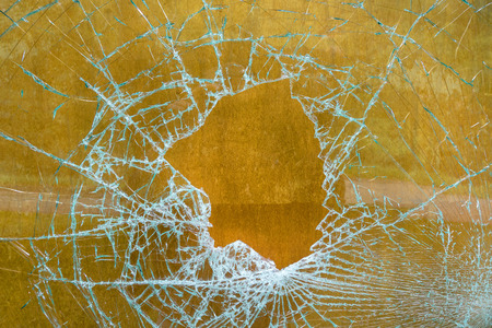Smashed glass pane in front of brown wood Stock Photo