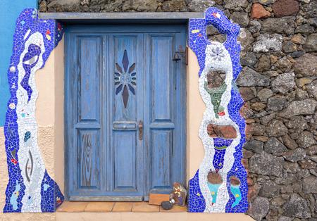 Blue door in artistically designed facade with mosaic