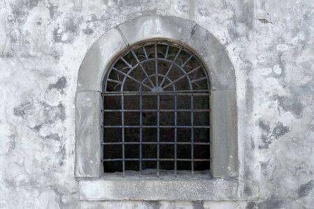 Semicircular lattice window in an old facade