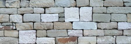 Old stone wall made of square natural stones