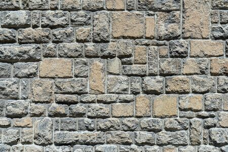 Old gray brown stone wall of rough, protruding natural stones