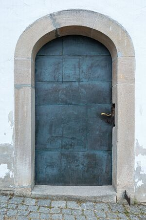 Old circular metal door with stone arch