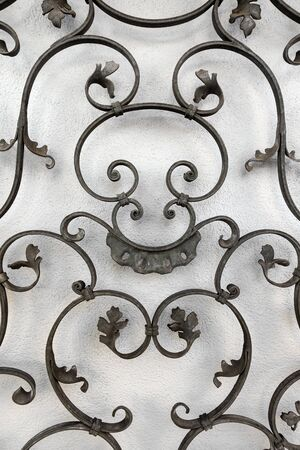 Artful grid made of wrought iron in front of a white wall